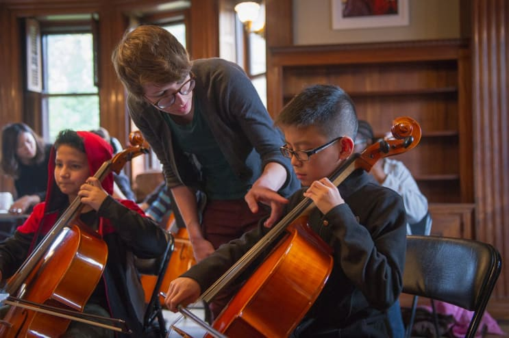 Graduate student teaching young cellists