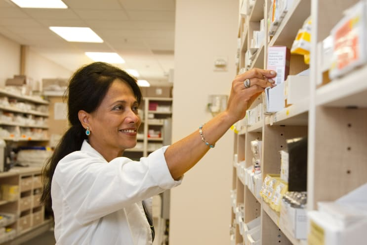 A female pharmacist is selecting a drug from the pharmacy inventory.