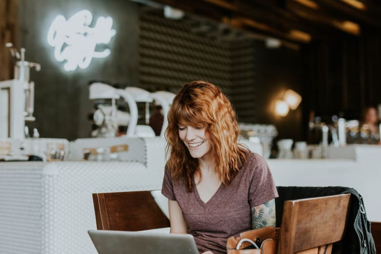Tattooed woman with laptop