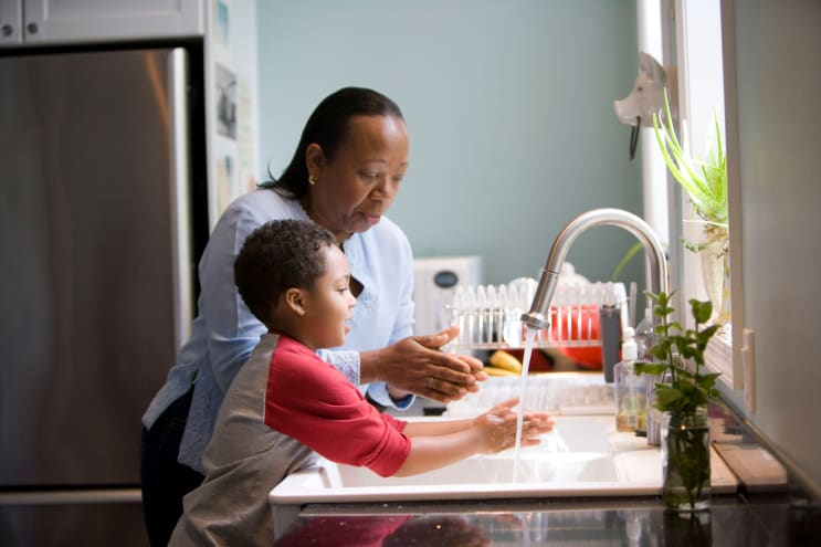 This African-American mother was shown in the process of teaching her young son how to properly wash his hands at their kitchen sink, briskly rubbing his soapy hands together under fresh running tap water, in order to remove germs, and contaminants, thereby, reducing the spread of pathogens, and the ingestion of environmental chemicals or toxins. Children are taught to recite the Happy Birthday song, during hand washing, allotting enough time to completely clean their hands.