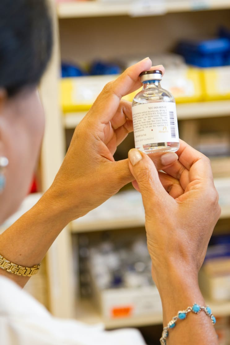 A female pharmacist is examining a vial in a pharmacy.