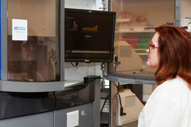 A technician performing an RNA-sequencing experiment on the Life Technologies 5500XL sequencer at the Advanced Technology Research Facility (ATRF), Frederick National Laboratory for Cancer Research, National Cancer Institute.