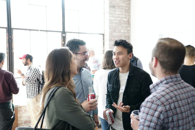 people having a conversation, talking, and smiling after an event in an open lobby