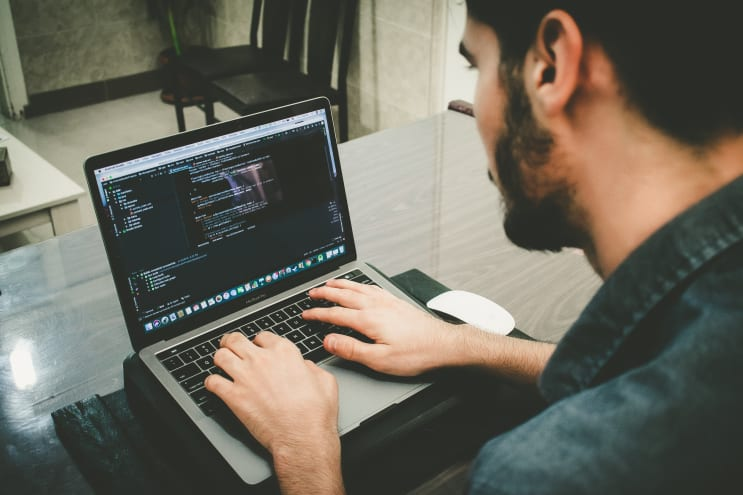 Person coding with MacBook Pro