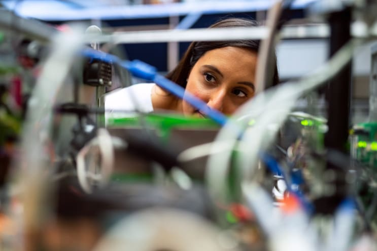Female space operations engineer inspects rover components