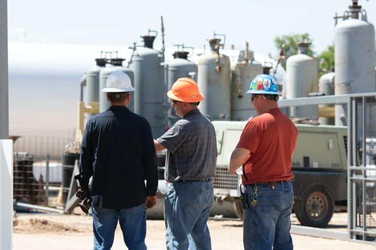3 men discussing equipment wearing hard hats.