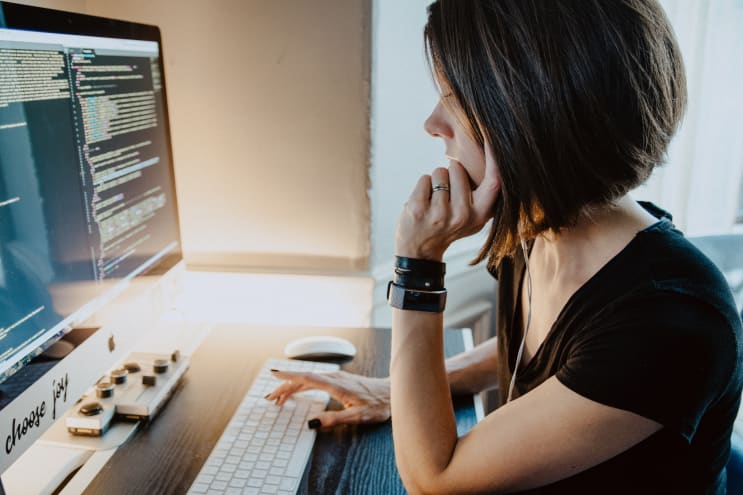 Woman sitting at a desk in front of coding computer screen