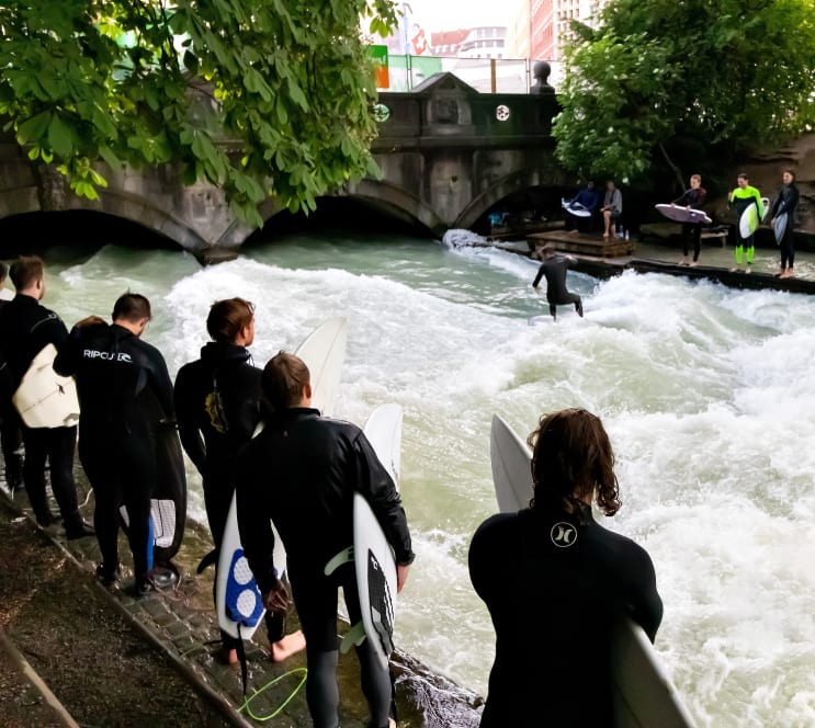 Surfers in Munich? Yes! Surfing waves on the Eisbach river at the entrance of the Englischer Garten.