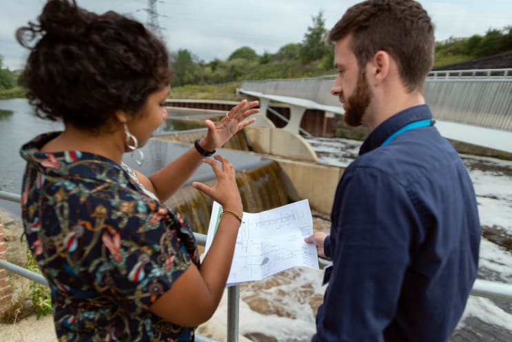 Female civil engineer discusses weir plans with colleague