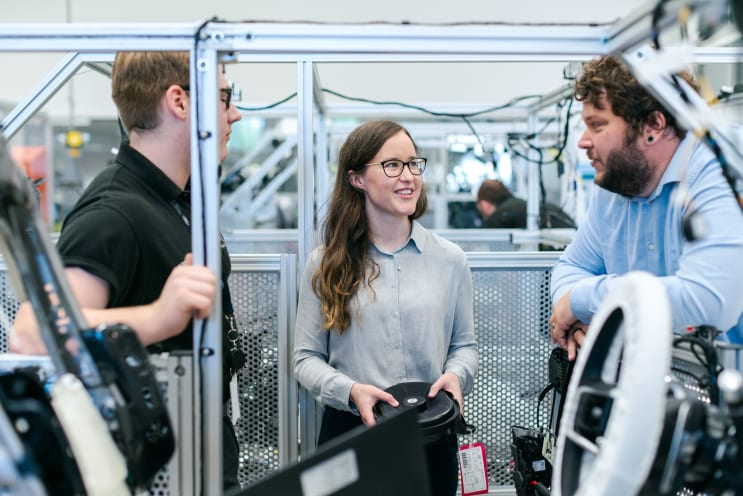 Female electronics engineer tests vehicle sound systems with team