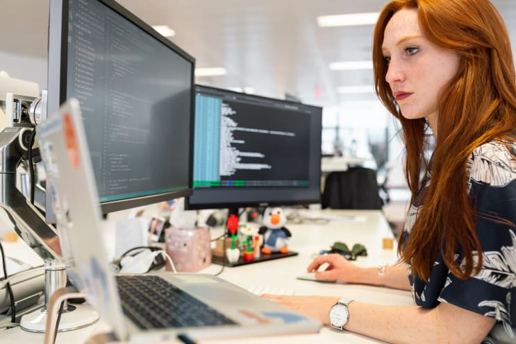 Female software engineer codes at computer