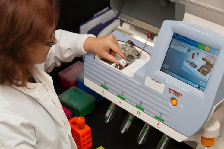 A female lab technician loading a semiconductor DNA sequencing chip used to identify specific cancer mutations in an individual. Photo taken at the Advanced Technology Research Facility (ATRF) at the Frederick National Laboratory for Cancer Research, National Cancer Institute.