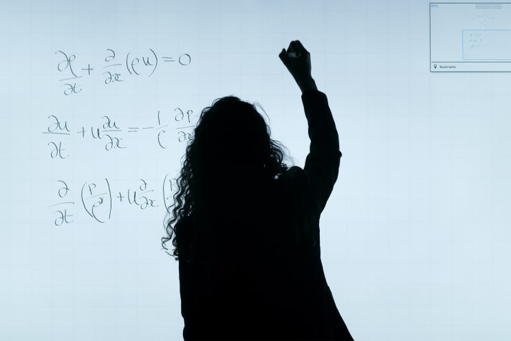 Female aerospace engineer writes equations
