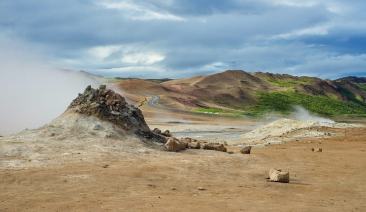 on a cloudy day at hverarönd, near námaskarð in north iceland,  a fumarole belches out noxious sulfuric gasses.