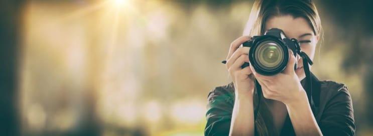Retrato de um fotógrafo que cobre seu rosto com a câmera.