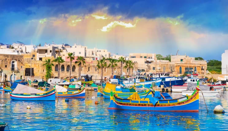 Marsaxlokk village harbor of Malta, illuminated by sunset light