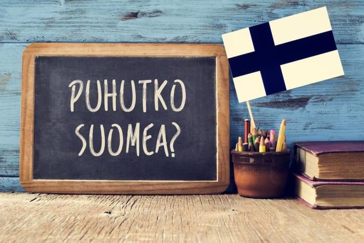 eine Tafel mit der Frage puhutko suomea, sprichst du Finnisch? geschrieben in Finnisch, ein Topf mit Stiften, einige Bücher und die Flagge von Finnland, auf einem Holzschreibtisch
