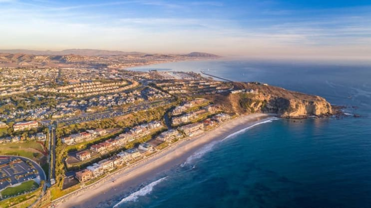 Aerial view of California coast and Dana Point harbor in Orange County on a sunny day.